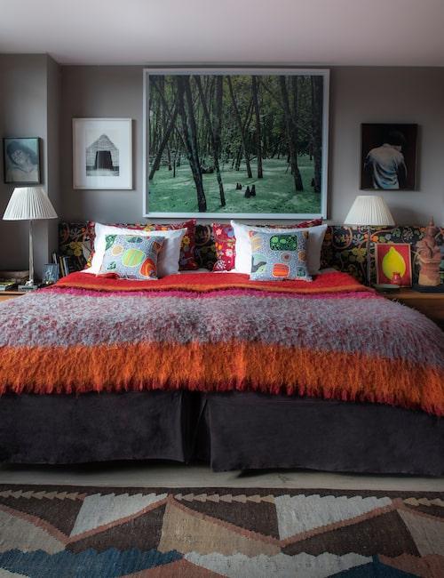 Även Alejandros sovrum är målat elefantgrått. Här kombinerat med varma och färgstarka textilier. Sänggaveln är klädd i klassiska Josef Frank-mönstret Baranquilla och går längs hela väggen vilket skapar en inbonad känsla. Över sängen hänger ett fotografi av amerikanska konstnären Kerry Tribe.