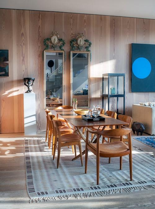 Matsalen är en förlängning av salongen i den öppna planeringen. Matbord och stolar av Hans Wegner i originalskick. Mattan är en grå Salerno av Märta Måås-Fjetterström. På de träklädda väggarna sitter två ovanliga speglar inköpta på Bukowskis.