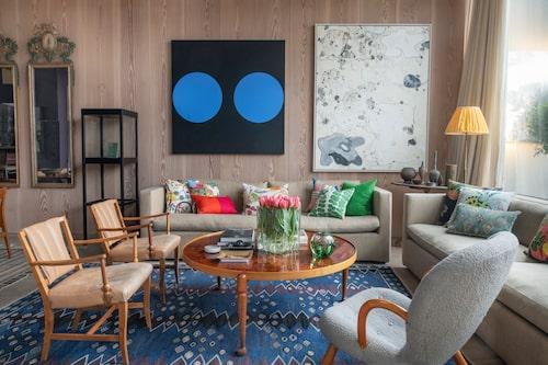 På salongens panelade väggar hänger oljemålningar av Ann Edholm och amerikanen Carter. På bordet står Alvar Aaltos vågformade glasvas från 1920-talet, den ursprungliga modellen till dagens moderna version. Den gröna runda vasen är en fiskgraalvas av Edward Hald.