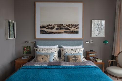 Gästrummets elefantgrå väggfärg harmonierar fint med det turkosa sängöverkastet i mohair. Ovanför sängen hänger ett konstverk av Edgar Esser. Sängborden är gamla telefonbord av Josef Frank som pryds med keramik av Stig Lindberg.