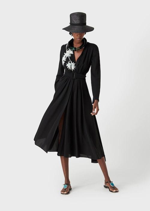 Meghans svarta klänning kommer från Armani.