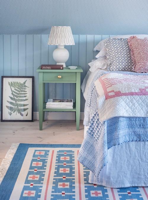Blåmålad pärlspont syns även i ett av gästrummen, här matchad med tapet från Helene Blanche. Mattan är egen design, liksom kuddarna Faye och Barbro. Quilten på sängen är ett av Cathys inköp från USA.