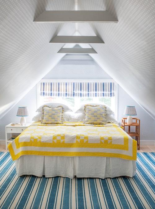 Det soligt inredda gästrummet på övervåningen har vitmålade takbjälkar, matta i Cathys egen design och ett gult quiltat överkast från USA. Kuddarna matchar i Cathys tyg Marianne. De randiga hissgardinerna fyndade Cathy på Blocket och de båda olika nattduksborden är köpta på loppis.