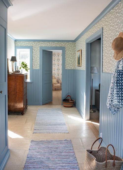 Hallen har försetts med blå panel och Cathys tapet Blanche. Trasmattor från Helena Rääf.