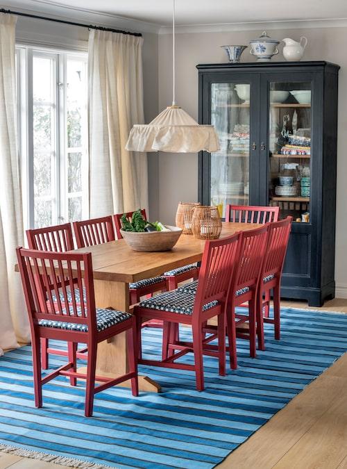 Matplatsens klassiska Leksandsstolar har målats röda och klätts med Cathys tyg Faye. Taklampa från Blue window inredning på Lidingö. Mattan är specialdesignad av Cathy. I det antika skåpet förvaras porslin och mönstrade bordsdukar.