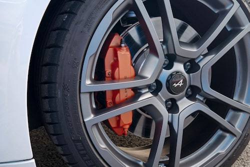 A110S har ett kraftigare bromspaket som standard och orangea bromsok.