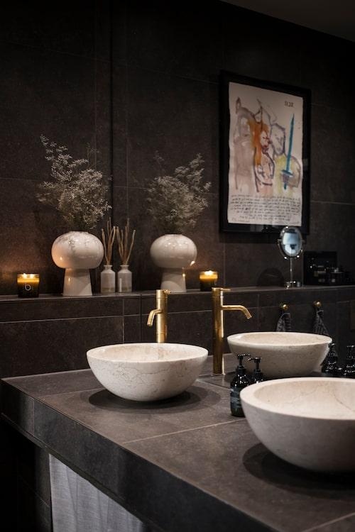 """Det lyxiga badrummet med Louises favoriter i hemmet – handfaten. """"De är så vackra, jag skulle vilja ta med mig dem om vi flyttar!"""" Hon minns inte varifrån de kommer, men liknande finns hos bland andra Gemlook och Viadurini. Kaklet som Louise valde är mörka, stora plattor på 60x60 cm, vilket hon menar är ett sätt att få badrummet att se större ut. Även den gigantiska spegeln hjälper till. Tavla av Ulf Lundell. Vas, H&M Home, doftljus, Bedford."""