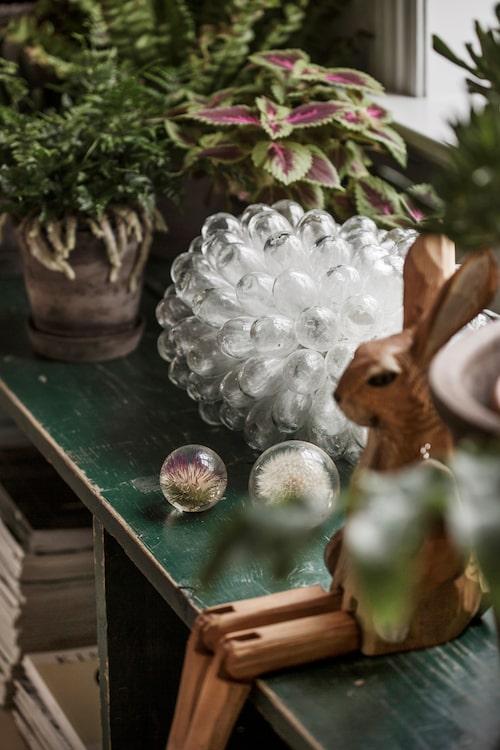 Träkaninen och de små glasbollarna med frökapslar är från Artilleriet och lampan, Clusterlamp, säljer Elin i sin butik.