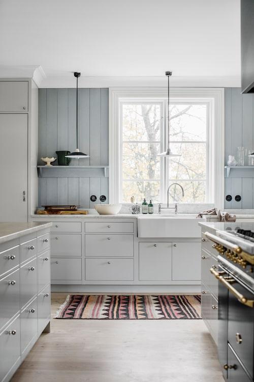 Köket kommer från Kvänum och är nybyggt. Trots moderna material och vitvaror har man landat i en känsla som minner om 1700-talets estetik. Köksknoppar, Byggfabriken, matta, Carpetvista.