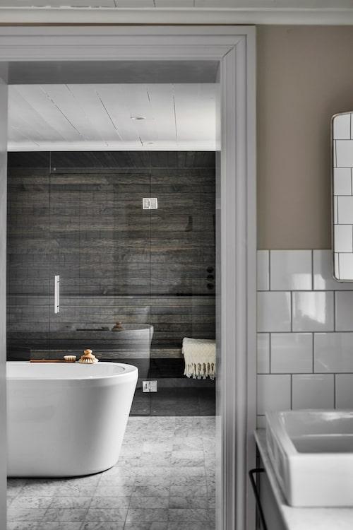 Det spatiösa badrummet är delat i två rum,varav det inre har en spa-avdelning med bastu och ett fristående badkar från Nordhem. Väggpanelen är behandlad med bastulasyr från Tikkurila.
