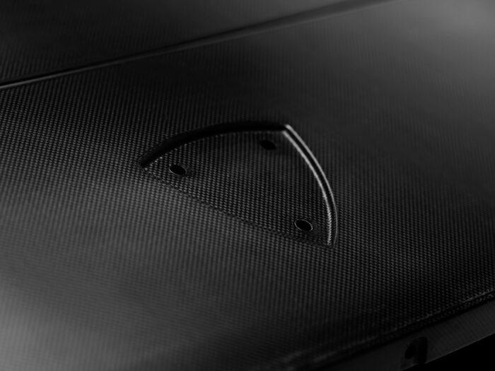 Emblemets yta strax framför huvkanten. Volvos järnmärke var på originalet placerad i ett sköldformat märke.