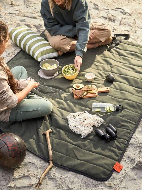 Vattentäta picknickfilten Fjällmott kan enkelt rullas ut och ihop igen. Kommer med handtag och kan bäras som en väska.