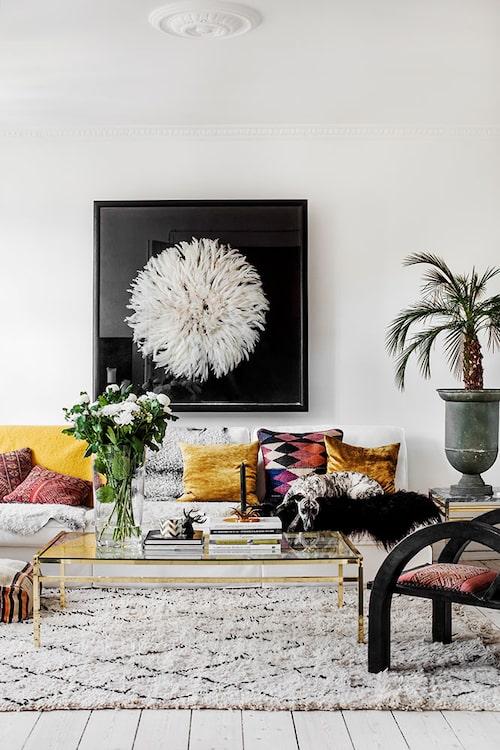 På väggen en inramad afrikansk jujuhatt av strutsfjädrar, köpt hos Mustapha Blaoui i Marrakech. Soffa, Ikea, mässingsbord med glasskiva, loppis, fåtölj och Beni Ourain-matta från Marrakech. Kuddar, loppis och Marrakech.