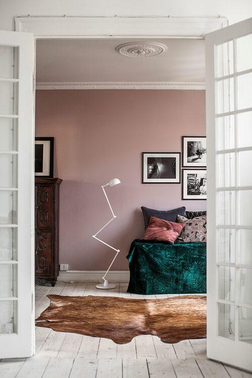 Från vardagsrummet går man in genom vackert spröjsade dörrar till kontoret gästrummet där väggarna målats gammalrosa. På väggen sitter svartvita fotografier från parets resor i San Francisco och på Korsika. Den vita lampan är köpt på Home & cottage i Norge. Koskinn, Ilva.