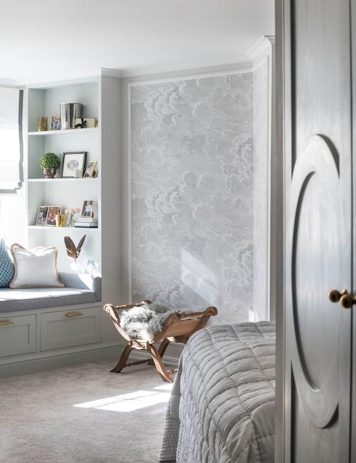 Thereses och Filips rymliga sovrum känns som en minisvit med mjuk heltäckningsmatta, inbjudande inbyggd sittplats och smart förvaring.