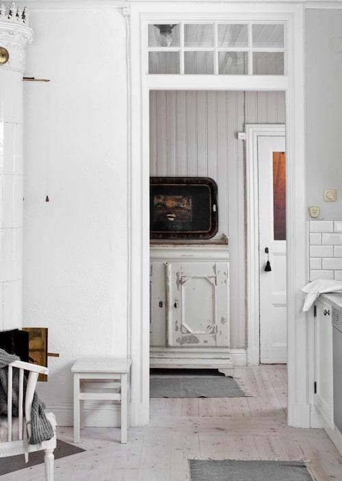 Fönstret i öppningen mellan kök och serveringsgång har Anna och Bo låtit sätta in. Skänken är inropad på bondauktion i Sala och pinnstolen hittade Bo i Mölle. Där kakelugnen står fanns tidigare en vedspis.