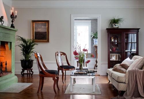 Huvudpjäs i vardagsrummet är den pampiga eldstaden i grön marmor. Howardsoffan är köpt på Bukowskis. Göteborgsstolarna i mahogny är arvegods, och soffbordet med kalkstensskiva, från Dux interiör. Vitrinskåp från Raja.