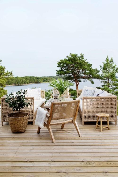 Uterum med sittbänkar i teak som satts ihop till ett bord.Rottingsoffor och stolar, Formlagret. Plädar, kuddar, pall och lykta från Tine K home.