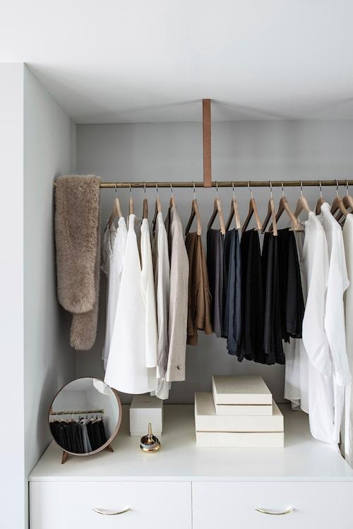 Lindas och Fredriks kläder tar plats på mässingsstänger upphängda i läderremmar. Undertill står bänkskåp från Ikea med lådor. Mässingshandtagen är köpta secondhand, liksom den lilla runda spegeln.