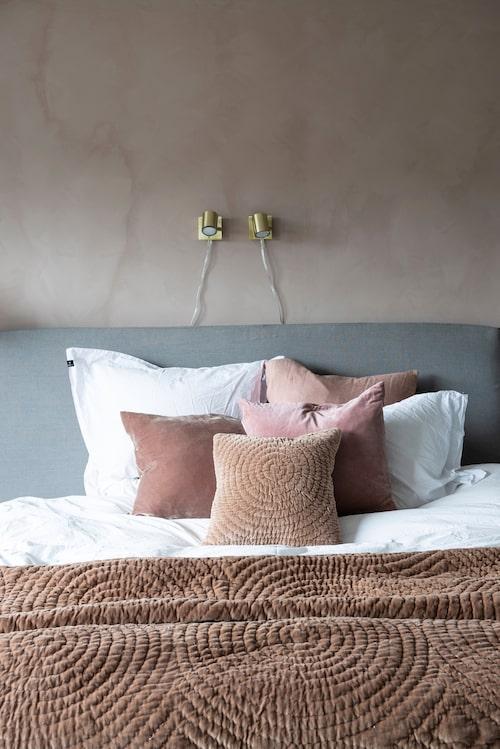 Föräldrasängen är en inbjudande plats i pudrigt rosa toner där familjen ofta samlas för att läsa och mysa. Säng från Dux, sänggavel med tygöverdrag, sängkappa och sängkläder, allt från Himla. Överkast, Broste Copenhagen. Kuddarna kommer från Broste Copenhagen, Himla, Frejas boning och Housedoctor. Vägglampor från Markslöjd.