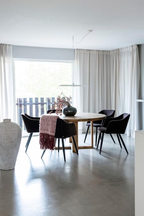 Fönster ända ned till golvet och gardiner draperade från taket känns lyxigt.Den tunna taklampan Alma, från Wästberg, skymmer utsikten minimalt.