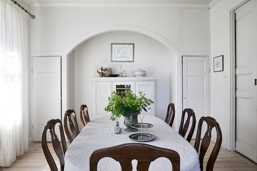 Matrummet är möblerat med ett gustavianskt matbord och stolar från Allinwood. På bordet en bukett daggkåpor från trädgårdsrabatterna.