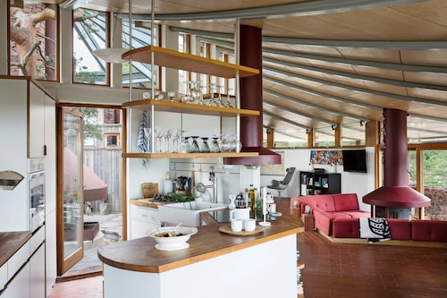 """Med sitt tydliga listverk öppnar sig innertaket likt en solfjäder och ger huset en """"toppig"""" känsla. Integrerat kök och vardagsrum. Den röda soffan är platsbyggd. Hopvikt svartvitt tyg över soffan, Marimekko. Tekanna och muggar, Design Kristina Stark."""
