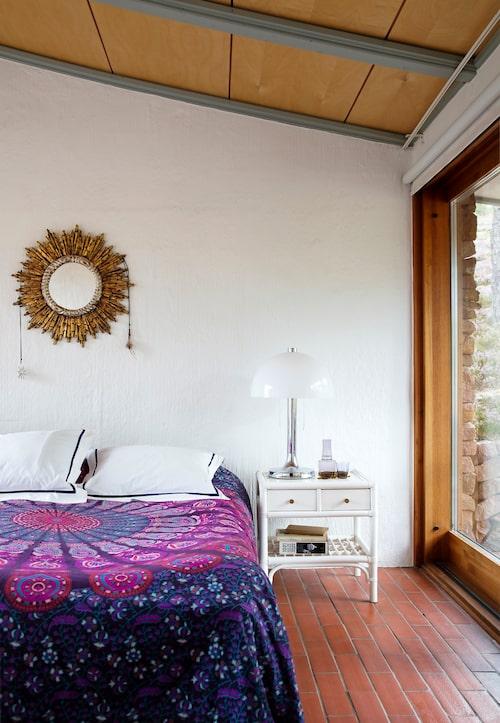 Tinas sovrum bjuder på spännande linjespel och rejäl takhöjd. På väggen ovanför sängen hänger en spansk solspegel. Sängbord, Dux, lampa, Fagerhult, glas, Kaj Franck för Iittala. Överkast från Spanien, örngott, Lexington.