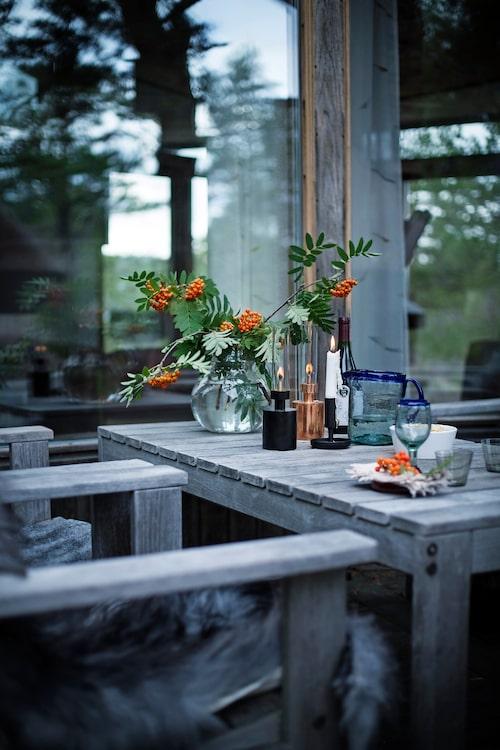 Uppdukat till middag i uterummet under den milda höstkvällen. Fotogenlyktor, Klong/Asplund, glaskannan är mexikansk från 70-talet. Vit skål Still life samt svart ljusstake Lux, Design Kristina Stark.