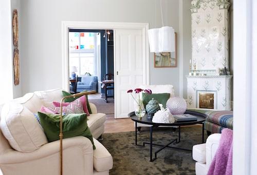 Vardagsrummets kakelugn är skir och romantisk i tonen.