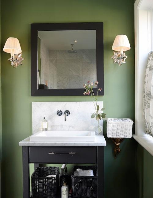 Gästbadrummet har fått grönmålade väggar, Calke green från Farrow & Ball. Inredningen är från Kvänum, lampetter, Vaughan/Cadoro. I den vita korgen ligger vikta gästhanddukar i prydlig rad.