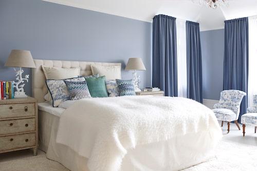 Det sägs att blått ger lugn och därför är en kulör som passar perfekt i sovrum. I föräldrarnas sovrum är väggarna målade i Gustaviansk blå, från Jotun. Sammetsgardiner från Lizzo/Tibbey&co. Två antika emmor har klätts i toile de Jouy, från Canovas/Cadoro.