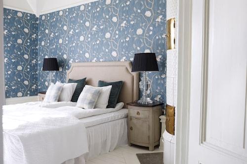 Gäster i familjen får sagolik vila under klassiska tapeten Snowtree, Colefax & Fowler. Sänggaveln i beige linne från In your dreams, sängbordet är köpt på auktion och sänglampor från holländska Eichholtz.