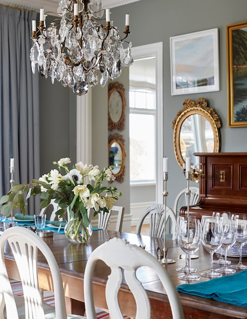 Den ovala spegeln är gustaviansk, och i vardagsrummet intill syns ytterligare två 1700-talsspeglar. På bordet tabletter och servetter i linne, från Svenskt tenn.