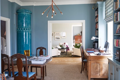 En turkos glaserad kakelugn lyser upp arbetsrummet. Skrivbord med stol är arvegods och det större bordet används även av familjens två barn. De inbyggda bokhyllorna är målade i samma färg som väggarna, Oval room blue från Farrow & Ball. Bokhyllebelysning från Besselink & Jones, taklampa Kvist, Örsjö belysning.