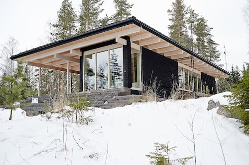 Det svartmålade huset (utanpå) har en nästan helt glasad fasad mot sjön.