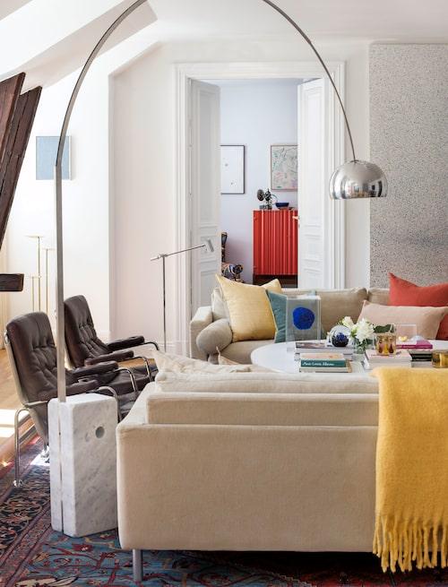 Över Eilersensofforna och Duxfåtöljerna i läderklädsel böjer sig Castiglionis Arcolampa. På väggen till höger, konstverk av Emanuel Röhss. Bakom dörrarna skymtar Svenskt tenns korallröda skåp Wellpapp.