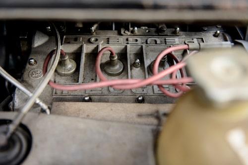 Under den fast monterade hatthyllan, snett in till höger, sitter motorn – på tvären ute vid sidan. Märkligt.