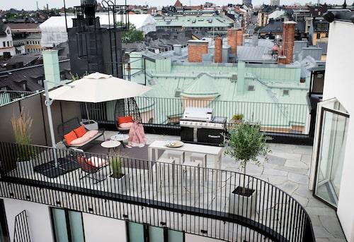 Från övre terrassen blickar man mot den nedres moderna uteplats.Det stora parasollet ger effektivt skydd, från Persiennkompaniet. Gruppen med barstolarna kommer från Classic garden. Sittgrupp och gunga från Kettal.