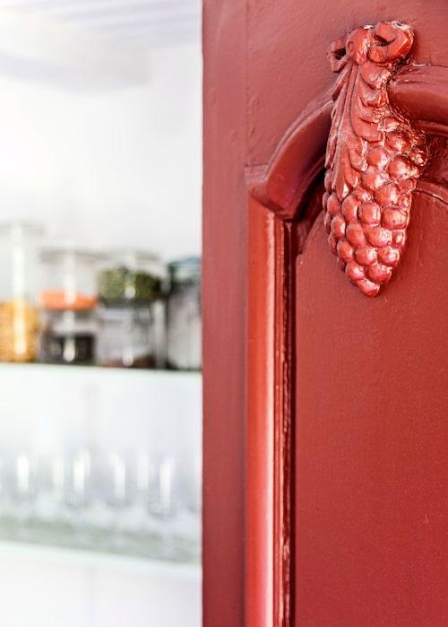 Detalj av pardörr till köket med en snidad vindruvsklase.