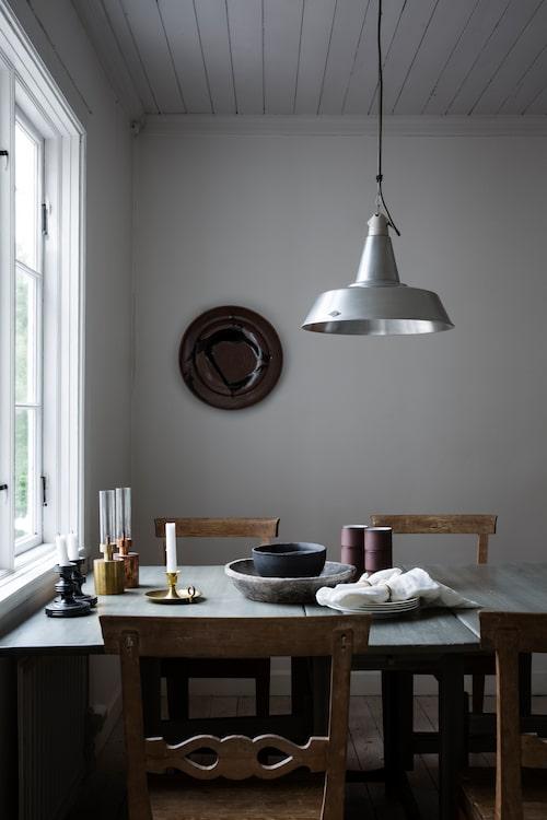 Keramikfat på väggen av Kennet Williamsson. Bord och stolar är antika, stolarna kommer från Ulrikas morföräldrar. Ljuslyktor i mässing och koppar från Klong. Muggar i keramik av Jonas Lindholm. Antika svarta ljusstakar i porslin från Gefle porslinsfabrik.