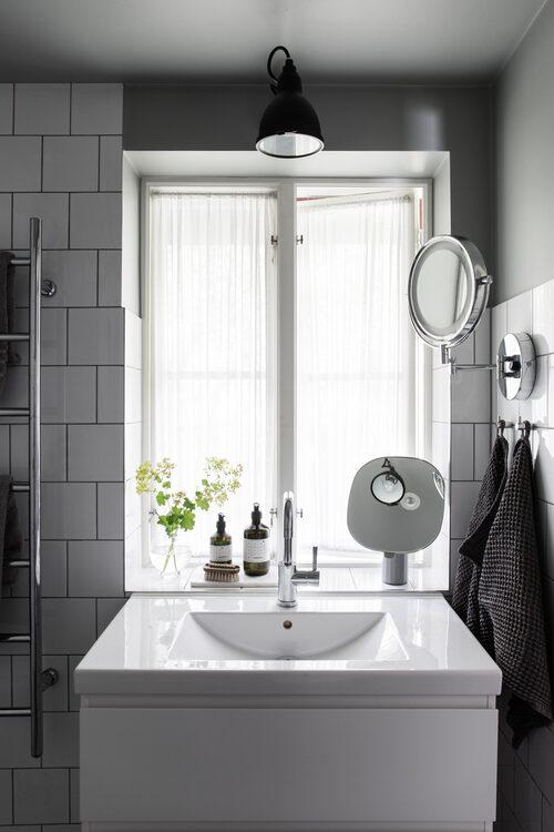 Efter att tidigare bara ha haft utedusch njuter familjen nu av det nya badrummet som går i grått och vitt och har fått klassiskt 15 x 15-kakel. Vägglampa från Lampe gras.