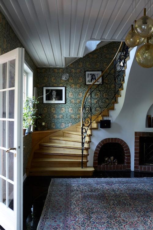 I hallen välkomnas besökaren av eldstad, vackert svängd trappa, persisk matta och tapet med William Morris-mönster. Trivseln infinner sig direkt! Taklampan är tysk och är köpt på Art n deco.