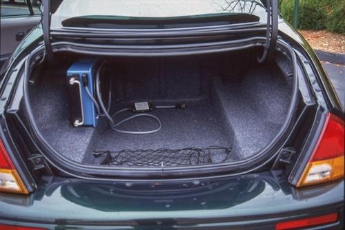 """Bagageutrymmet är utformat för att rymma två golfutrustningar. Till vänster i utrymmet skymtar den """"hemmaladdare"""" som följer med bilen."""