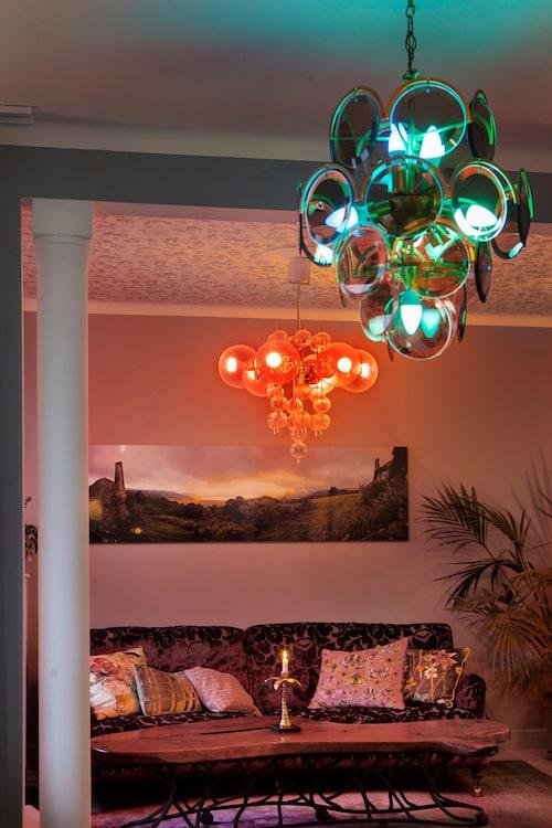 Med ljussättningen Hue från Philips omvandlar Alexandra och dottern Melina hemmet till ett disco eller ett färgglatt sagospektakel. Soffa, NK, kuddar, Designers guild, ljuskrona i förgrunden, Bukowskis, ljuskrona i bakgrunden, Domino antik.
