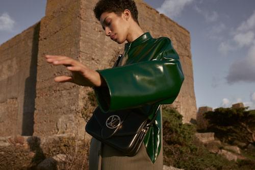Tvåfärgad kappa av ull/läder, pris vid förfrågan, Louis Vuitton. Axelremsväska av läder med guld-färgade detaljer, 31 500 kr, Louis Vuitton.