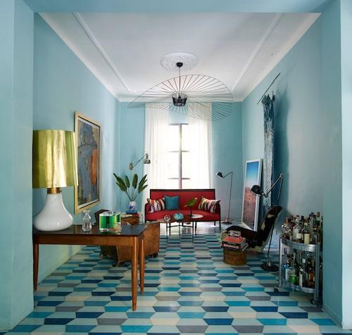 Något nytt, något gammal. Den höga metalliska bordslampan är ett omgjort vintagefynd från Berlin som fått en ny lampskärm designad av Caitlin. Taklampa av Constance Guisset. Den röda soffan är köpt på auktion i Paris, sidobordet, från en lokal antikhandlare.