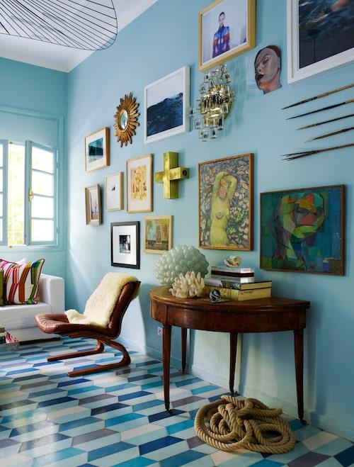 Eklektisk mix. Vardagsrummet har fönster åt motsatta håll. Läderfåtölj från 70-talet av Ingmar Relling, inhandlad i Berlin. Parets förmåga att mixa olika perioder och stilar märks också i tavelväggen där toner i guld och blått knyter ihop paletten.
