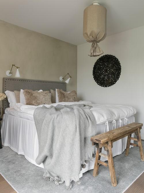 Husets enda sovrum går som resten av hemmet i mjuka naturtoner. Den fina sänggaveln har Yvette gjort själv, den smala bänken är från Snowdrops Copenhagen.
