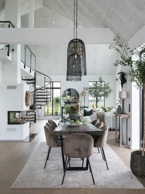 Runt Yvettes och Anders mycket rustika matbord från PB Home vill man sitta länge och mysa i de stoppade stolarna. I det stora, ljusa kombinerade köket och vardagsrummet i deras nybyggda hus trivs även växterna som blivit härligt stora. De högsmala taklamporna från Lene Bjerre understryker takhöjden.